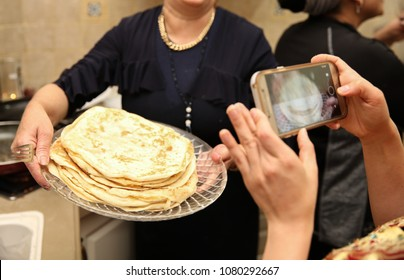 Woman holds the Jewish ethnic food called 'mufleta' on a platter while someone takes a cell phone picture. This food is traditionally made at the end of the Passover holiday