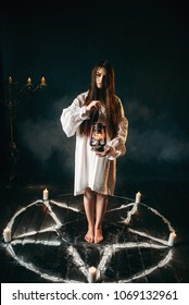 Woman holds kerosene lamp, pentagram circle, magic