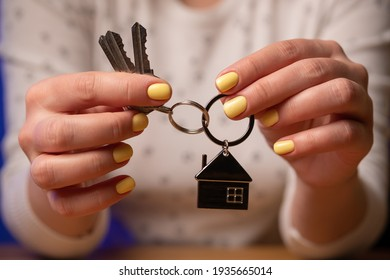 Woman holds keys from new house. Family buys a house or apartment.
