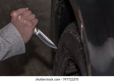 A woman holds a knife in her hand and wants to sting with it in a car tire. Slashing into a car tire. Concept: vandalism and crime