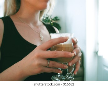 Woman holds latte in a cafe.