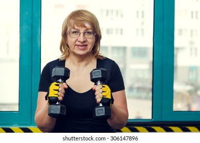 Woman holds up lifting dumbbells. Client fitness center. Woman - fitness gym. Senior exercising at gym. Old woman exercising with weights at gym. Adult woman holding dumbbell lifting up. Sport woman.