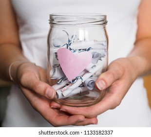 Woman holds a mason jar with pink heart and rolled up notepads in her hand