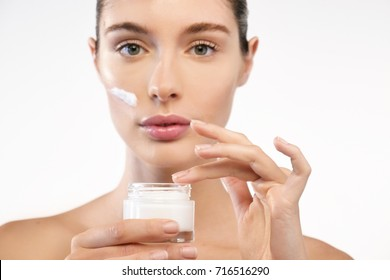 A woman holds a moisturizer in her hand and spreads it on her face and body to moisturize her skin and wrinkle from impurities. Concept of: beauty, body care, skincare.