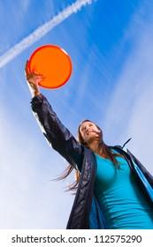 Frau hält eine orangefarbene Scheibe und achtet darauf, zu werfen, blauer Himmel auf dem Hintergrund
