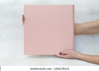 a woman holds a photobook the person looks at the photo book sample photo album  photo book with  leather cover  sample photobook