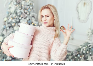 A woman holds presents in her hands, in her other hand a bitcoin coin.