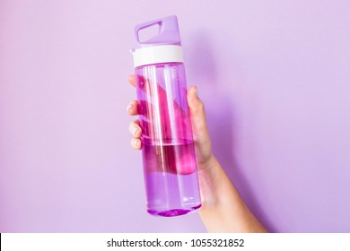 A woman holds a purple water bottle in her hand for sports.  On a bright purple background. Healthy lifestyle and fitness concept