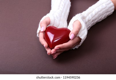 A woman holds a red heart in her hands