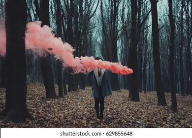 Woman holds up red smoke flare to signal for help in the middle of nature. Rainy forest in mist.