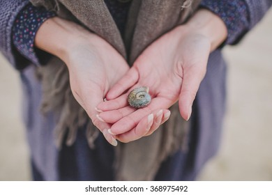 Woman holds sea shell in her hands