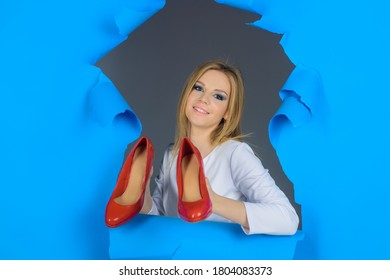 Woman holds shoes. Shoes sale. Beauty and fashion. Beautiful woman holds red shoes. Advertising. Discount and sale. Woman through hole in paper.