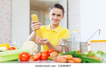 Woman holds and shows uncooked pasta