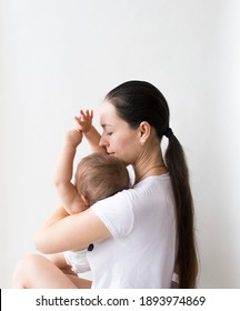 a woman holds a small child, mother and child on a white background, close-up. children's day,mother's day