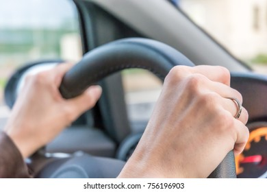 Woman holds the steering wheel tight while driving