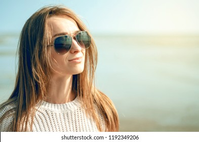 Woman holds sunglasses on the background of the sea sun sweater watch autumn cold