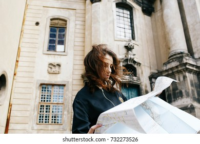 Woman holds touristic map in her arm standing before old cathedral