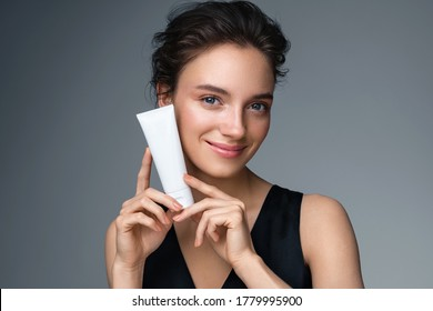 Woman holds tube with cosmetic cream. Photo of attractive woman with perfect makeup on gray background. Beauty concept