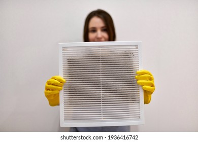 Woman holds ventilation grill with dust filter to clean it. Extremely dirty and dusty white plastic, harmful for health. Housewife in protective yellow rubber gloves and blue-grey uniform, blurred.