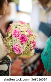 Woman holds wedding bouquet made of tiny daisies and pink roses