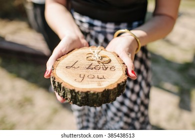 "Woman holds wedding rings on wooden holder with ""i love you"" words"