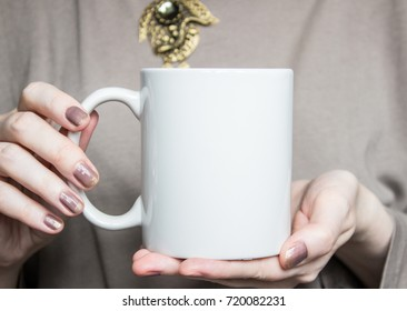 Woman holds white mug in hands. Design Mockup