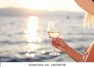 Woman holds wineglass with pink wine in hand on beach at summer background of sunset sea or ocean. Blond girl is straw hat is relaxing, drinking, traveling and enjoying life in romantic vacation.