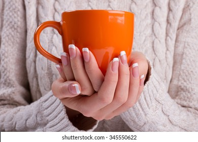 Woman holds a winter cup close up. Woman hands with elegant french manicure nails design holding a cozy mug. Winter and Christmas time concept.