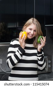 Woman holds a yellow and a green paprika in her hands while standing in the kitchen