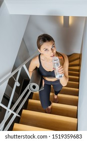 Woman holds yoga mat and bottle with water go up the wooden stairs of house from the steps, walking is good for health, move between floors on training, private two-storey house. Sun glare effect
