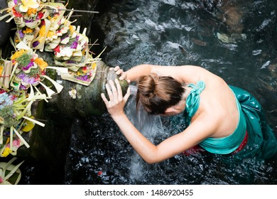 A woman at the holy spring water to praying at Pura Tirta Empul Temple, Bali Indonesia
