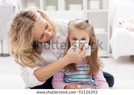 Woman at home blowing the nose of her little girl