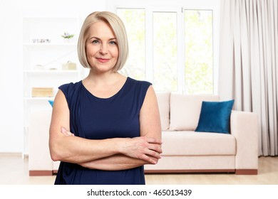 Woman at home in front of window relaxing in her living room