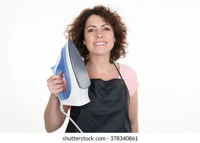 Woman at home holding up her household iron with a happy grin isolated