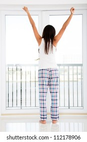 Woman at home just waking up and looking through the window