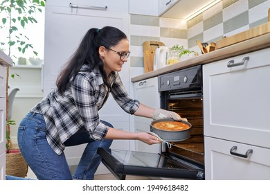 Woman at home in kitchen taking out hot apple pie from oven