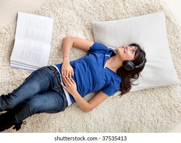 Woman at home lying on the floor listening to music