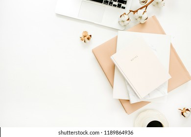 Woman home office desk with laptop, notebook, coffee cup, cotton branch on white background. Flat lay, top view minimal blogger workspace.