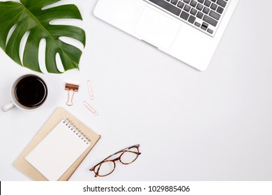 Woman home office desk workspace with laptop, tropical palm leaf, glasses, notebook and coffee cup on white background. Flat lay, top view. stylish female concept.
