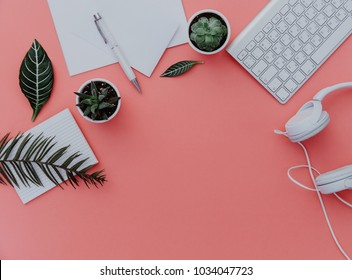 Woman home office desk workspace with laptop, headphones and plants over pastel. Flat lay, top view. stylish female concept.
