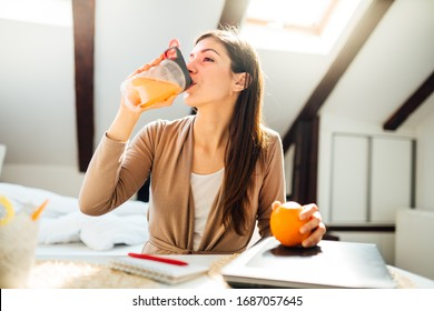 Woman in home office drinking orange flavored amino acid vitamin powder.Keto supplement.After exercise liquid meal.Weight loss fitness nutrition diet.Immune system support.Organic citrus fruit