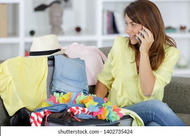 woman at home packing suitcase taking a phonecall