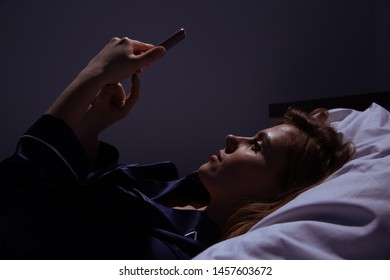 Woman at home with phone in the bed. Using mobile before going to sleep.