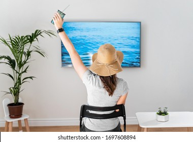 Woman at home pretending to be on the beach. TV screen. 2020 summer quarantine travel. Stay home