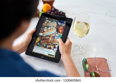 Woman at home relaxing ordering food online delivery takeout app on digital tablet device