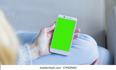 Woman at home relaxing reading on the smartphone with pre-keyed green screen
