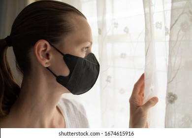 Woman at home in self isolation quarantine looking out window with face mask on. Coronavirus 2019-ncov.