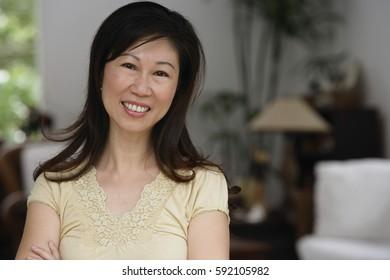 Woman at home, smiling at camera, head shot