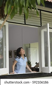 Woman at home, standing by window, looking out