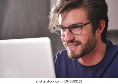 A woman at home uses her laptop to: send work mails, shop online, surf on social networks. Concept of: shopping, work, relaxation and technology.